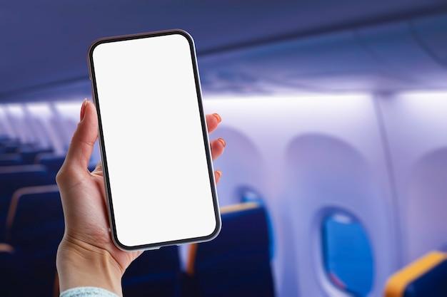 Ręka trzyma makiety smartphone z pustego ekranu wewnątrz samolotu.