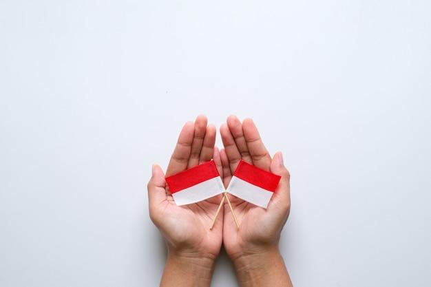 Ręka trzyma małą indonezyjski flaga narodowa. koncepcja dnia niepodległości na białym tle