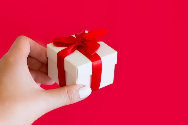 Ręka trzyma małe białe pudełko z czerwoną kokardą na czerwonym. prezent w kobiecej dłoni, miejsce