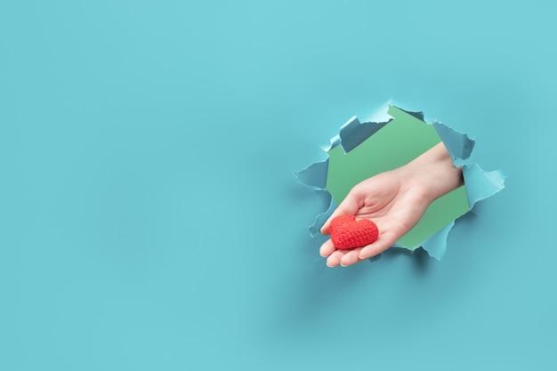 Ręka trzyma małe serce przez otwór w papierze. pojęcie miłości i opieki. skopiuj miejsce