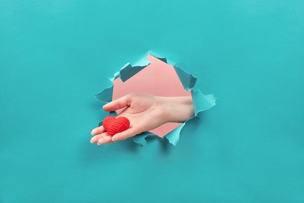 Ręka trzyma małe serce przez otwór w papierze. pojęcie miłości i opieki