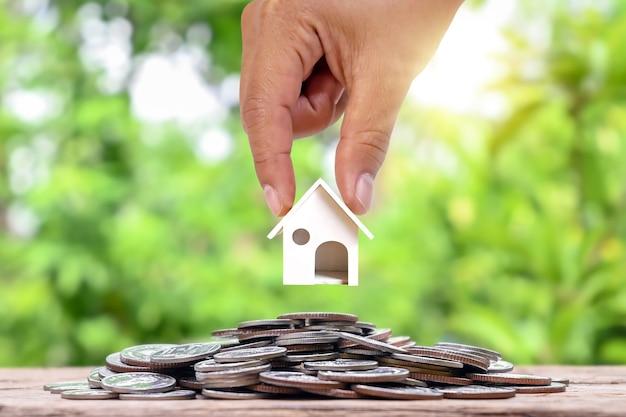 Ręka trzyma mały biały model domu umieszczony na stosie monet koncepcja inwestycji w nieruchomości