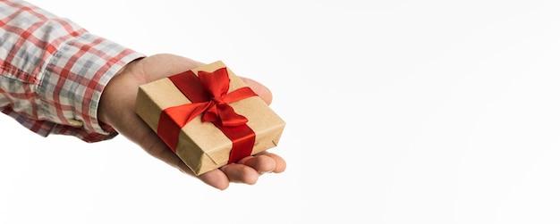 Ręka trzyma mały prezent z kokardą