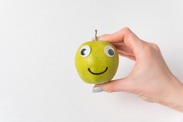 Ręka trzyma mały uśmiech apple z oczami googly. białe tło. koncepcja diety i odchudzania.