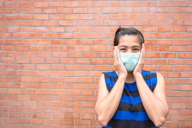 Ręka trzyma maskę na azjatyckim kobiecie stawia czoło tło ściana z cegieł.
