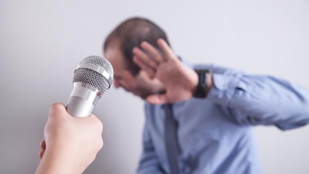 Ręka trzyma mikrofon. mężczyzna odmawiający wywiadu