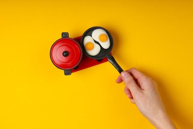 Ręka trzyma mini patelnię zabawki z jajkiem sadzonym na kuchence, żółta powierzchnia