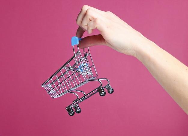 Ręka trzyma mini wózek na zakupy na czerwonym tle. koncepcja zakupów