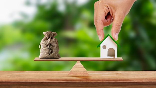 Ręka trzyma model domu i torby oszczędnościowej umieszczonej na wadze i rozmytym zielonym tle
