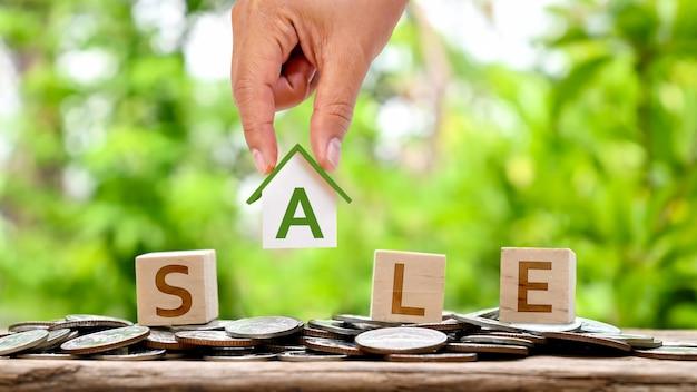 Ręka trzyma model domu i wiadomość o sprzedaży na drewnianym blogu koncepcja pożyczki domowej na inwestycję w nieruchomości
