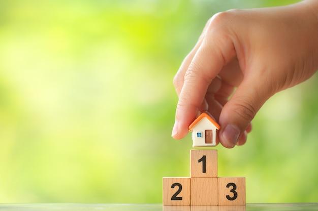Ręka trzyma model domu na pierwszym miejscu podium zwycięzcy