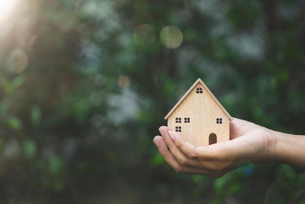 Ręka trzyma model domu na tle przyrody i inwestycji biznesowych dla koncepcji nieruchomości