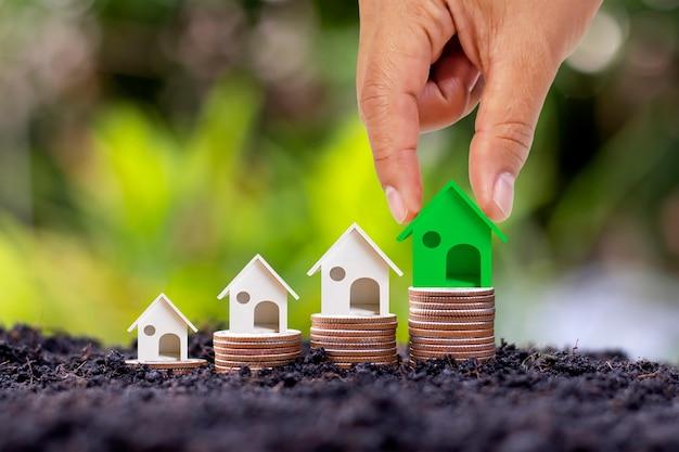 Ręka trzyma model zielonego małego domu umieszczonego na stosie monet koncepcji nieruchomości inwestycyjnych