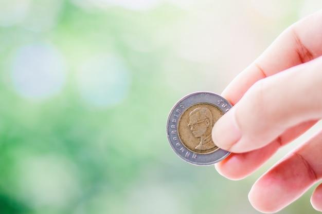 Ręka trzyma monetę, 10 bahtów waluty tajlandzkiej pieniądze