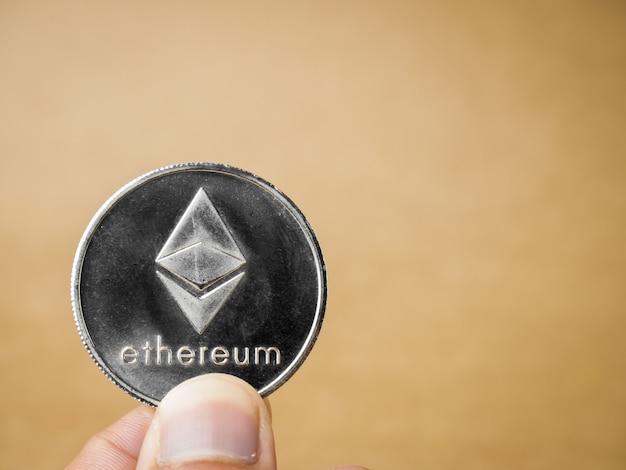 Ręka trzyma monetę eterową.