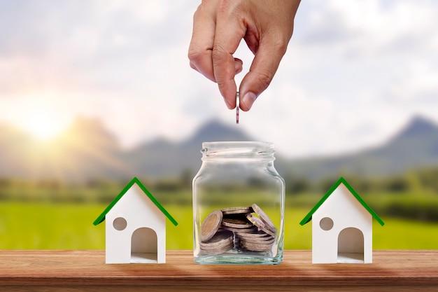 Ręka trzyma monetę w piggy bank i model domu na drewnianej podłodze, koncepcja finansowa. akcje firm i inwestycje w nieruchomości