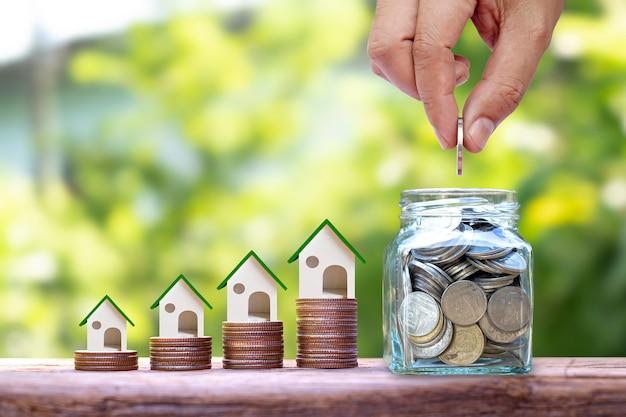 Ręka trzyma monety w słoiku do oszczędzania pieniędzy i modelu domu na stosach monet koncepcji pieniędzy