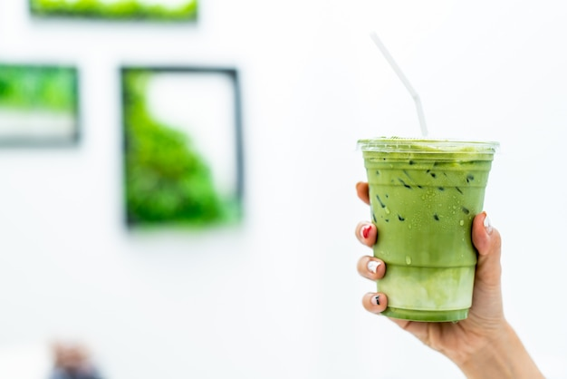 Ręka trzyma mrożoną filiżankę matcha latte zielonej herbaty