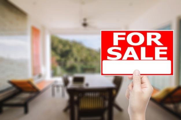 Ręka trzyma na sprzedaż znak domu z tłem wnętrza domu