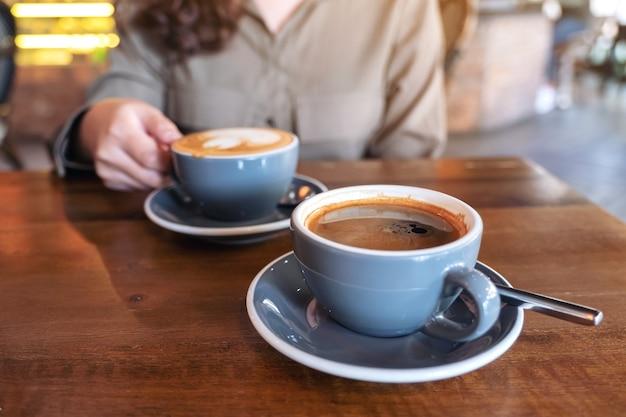 Ręka trzyma niebieską filiżankę gorącej czarnej kawy z inną filiżanką kawy latte na drewnianym stole w kawiarni