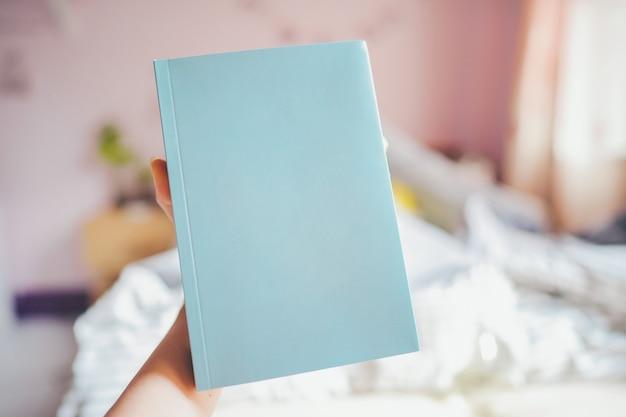 Ręka trzyma niebieską książkę z pustą okładką, w sypialni jest miejsce na tekst.
