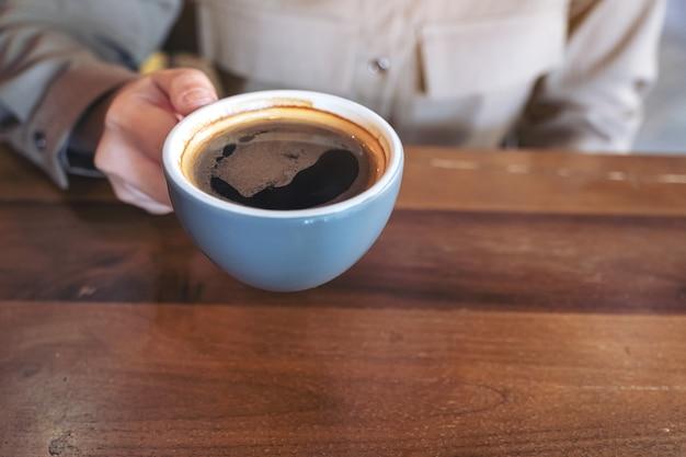 Ręka trzyma niebieski kubek gorącej czarnej kawy na drewnianym stole w kawiarni