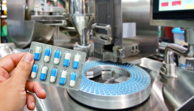Ręka trzyma niebieskie opakowanie kapsułki na linii produkcyjnej pigułki leku, przemysłowej koncepcji farmaceutycznej.