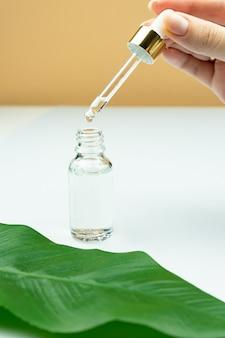 Ręka trzyma niemarkową szklaną butelkę z serum do skóry. zabieg nawilżająco-ujędrniający dla skóry. butelka na serum do twarzy z zakraplaczem. pojęcie kosmetologii i urody.