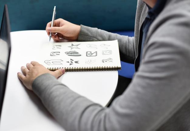 Ręka trzyma notatnik z drew marka logo kreatywne projekty pomysłów