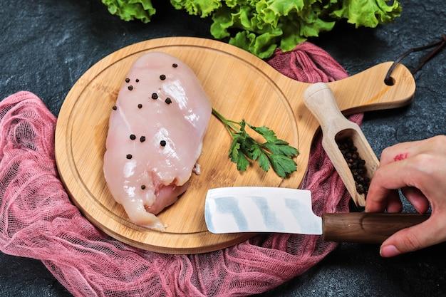Ręka trzyma nóż i kawałek surowego fileta z kurczaka na drewnianym talerzu ze świeżymi warzywami i obrusem.