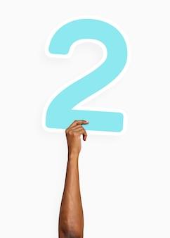Ręka trzyma numer dwa znak