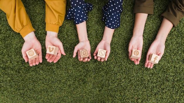 Ręka trzyma ogólnospołecznych medialnych app ikon drewniani bloki na zielonej trawie