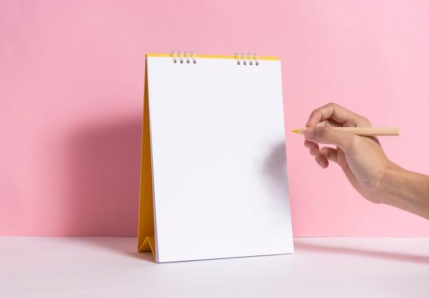 Ręka trzyma ołówek do pisania oznakowania na makieta papier spirala kalendarz na różowym tle.