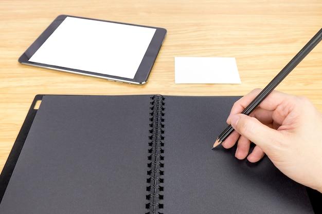 Ręka trzyma ołówek pisania na puste czarna księga z tabeli