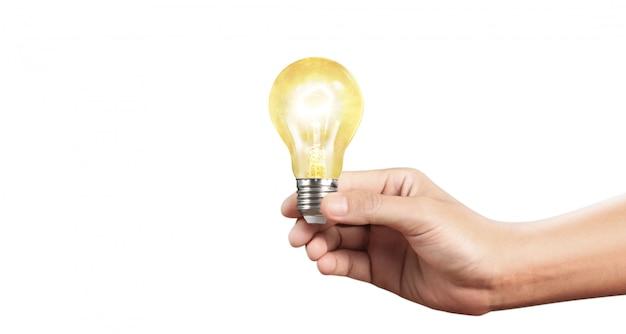 Ręka trzyma oświetloną żarówkę