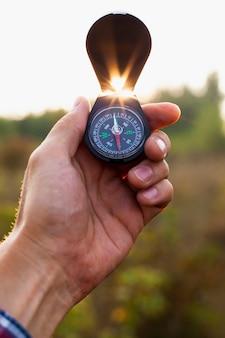 Ręka trzyma otwarty kompas w powietrzu