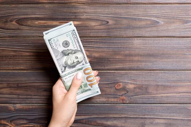 Ręka trzyma pakiet stu banknotów dolarowych na drewniane tła. koncepcja wynagrodzenia i płacy z miejsca na kopię.