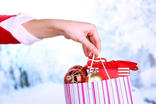 Ręka trzyma pakiet z kulkami noworocznymi i prezentami na tle śniegu