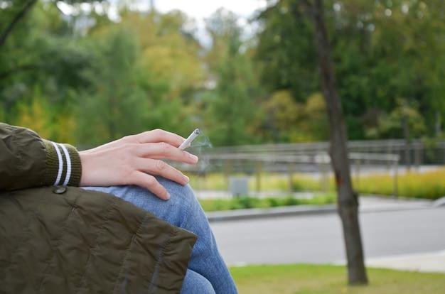 Ręka trzyma palącego się papierosa na tle widoków jesiennego parku miejskiego.