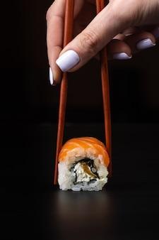 Ręka trzyma pałeczki sushi na czarnym stole.