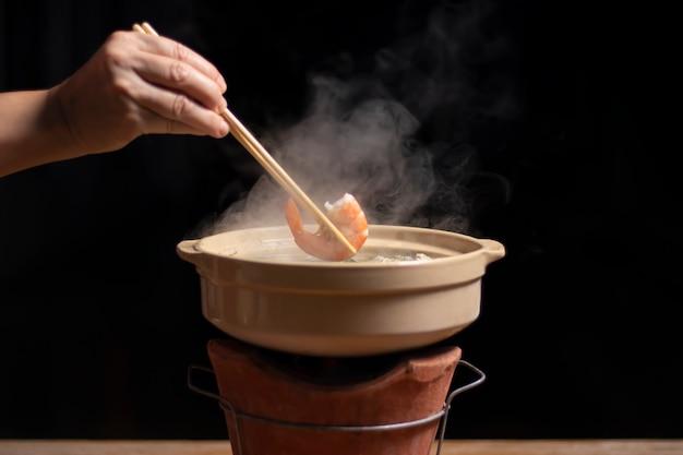 Ręka trzyma pałeczki z krewetkami na gorący styl tajski garnek.
