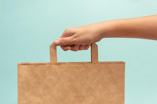 Ręka trzyma papierową brązową torbę ekologiczną na jasnoniebieskim tle.