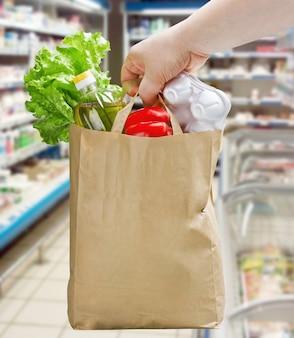 Ręka trzyma papierową torbę z artykułami spożywczymi