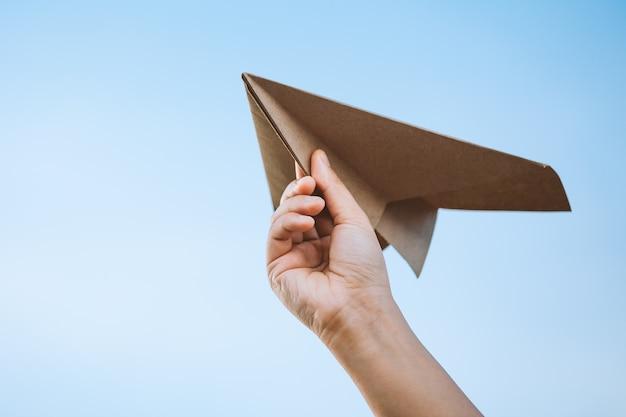 Ręka trzyma papierowego samolot przeciw niebu