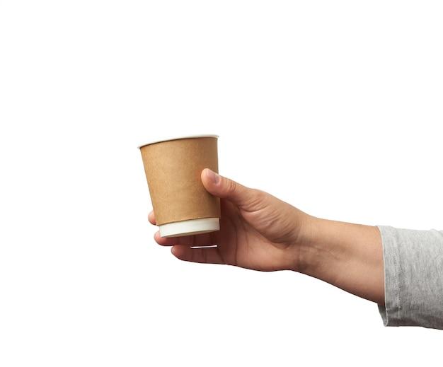 Ręka trzyma papierowy brązowy jednorazowy kubek do kawy i herbaty