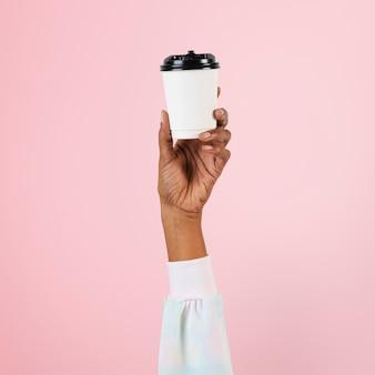 Ręka trzyma papierowy kubek do koncepcji żywności
