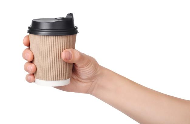 Ręka trzyma papierowy kubek kawy na wynos na białym tle.