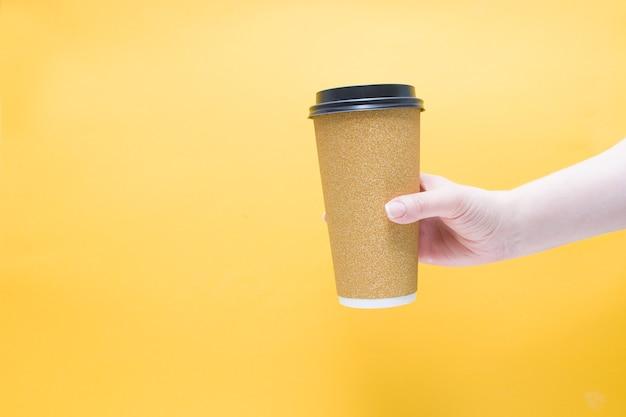 Ręka trzyma papierowy kubek kawy w złotym błyszczącym opakowaniu żółtym tle kopii przestrzeni