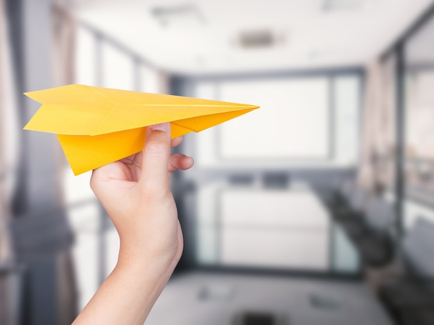 Ręka trzyma papierowy samolot na tle biura