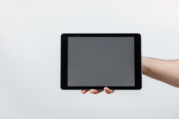 Ręka trzyma pastylkę z białym ekranem na bielu, odizolowywającym